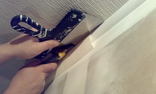 Обрезка обоев у потолка с помощью шпателя